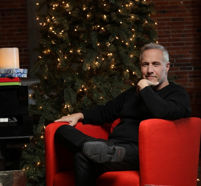 Jim Brickman Sitting on Red Chair with Christmas Tree In Background